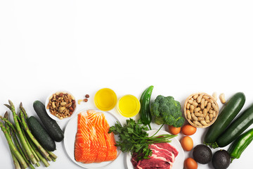 Ketogenic, keto diet, including vegetables, meat and fish, nuts and oil on white background with copy space