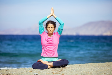 Caucasian young woman practicing yoga on beach