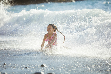 Happy girl playing in breaking waves on beach