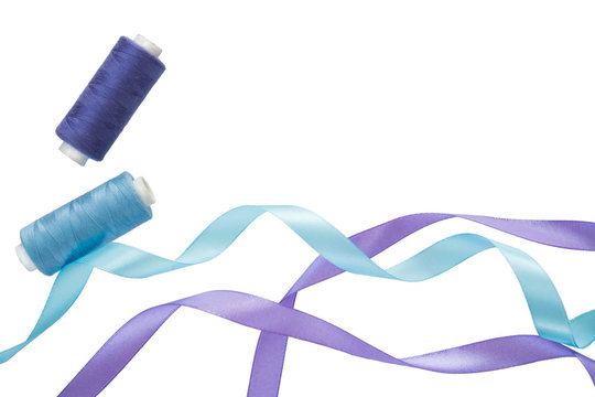Blue and purple curly satin ribbons, spools of blue and purple thread on a white. Horizontal banner with two satin ribbons and spools of thread. Copyspace. For fabric, sewing stores, tailoring atelier