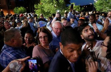Democratic presidential candidate Sen. Bernie Sanders takes photographs with supporters while trying to move through a crowd during Jim Clyburn's World Famous Fish Fry in Columbia