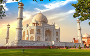 Wall Mural - Taj Mahal historic white marble mausoleum at sunset with moody sky and view of tourists at Agra, India