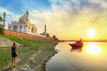 Wall Mural - Taj Mahal scenic sunset view on the banks of river Yamuna with woman tourist enjoying the view