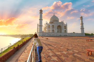 Fototapete - Taj Mahal Agra on the banks of river Yamuna at sunset with female tourist enjoying the view