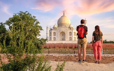 Wall Mural - Tourist couple enjoy Taj Mahal sunset view  from Mehtab Bagh. Taj Mahal is a historic monument  built on the banks of river Yamuna at Agra India.