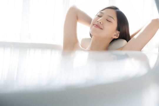 Young Asian woman relaxing in a bath . Female skincare concept