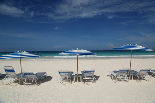 Beach chairs and umbrella on a beautiful Caribbean beach at Harbor Island, Bahamas