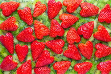 funny creative concept of sliced kiwi flower shape and strawberry heart shape like background