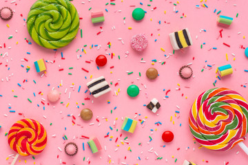 flat lay of festive background with assortment of colourful caramel candies with jelly and sprinkles over pink