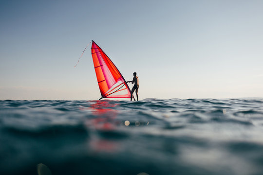 Surfer uplift windsurf board. Low angle view of windsurfer on the board