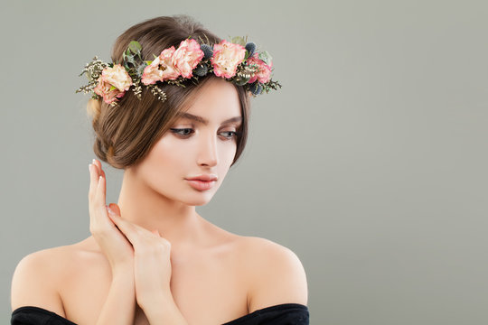 Pretty young woman wearing flowers wreath on gray banner background