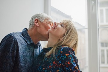 Hot and Sexy Middle-aged Woman Enjoying Kissing of Her Elderly Husband Standing near Opened Window inside Their Home. Couple with Age Difference