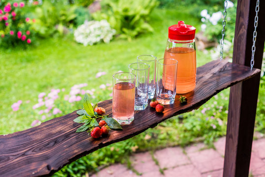 Glasses and jug of fruit juice. Summertime in the garden