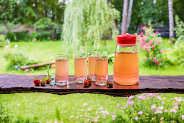 Four full glasses and jug of fruit juice, strawberries and mint on wooden table . Summertime in countryside.