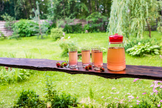 Long wooden table with four full glasses and jug of fruit juice, strawberries and mint. Summertime in countryside.