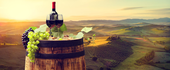 Fototapeta Red wine with barrel on vineyard in green Tuscany. Italy