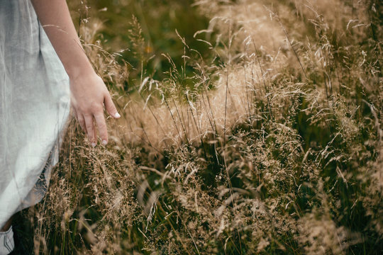 Stylish girl in linen dress gathering herbs and wildflowers in field, hand close up. Boho woman walking in countryside among grass, simple slow life style. Space for text. Atmospheric image