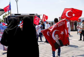 AK Party supporters wave flags with pictures of Turkish President Tayyip Erdogan in support of the party's mayoral candidate Binali Yildirim in Istanbul