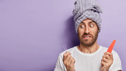 Surprised male model removes eyebrow hair with tweezing, uses nail file for doing manicure, afraids of beauty treatments, wears casual white t shirt, has wrapped towel on head, stands indoor Wall mural