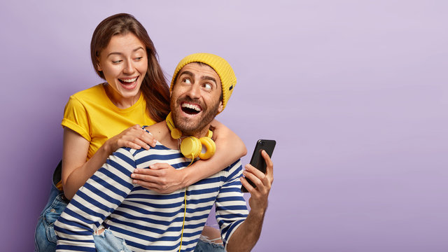 Happy couple have fun together, man gives piggyback to girlfriend, carries woman on back, holds smartphone, shows funny pictures in social networks, listens audio in headphones, pose over purple wall