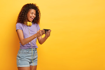 Sideways shot of happy lady with curly hair, holds mobile phone, watches funny movie online, has positive smile on face, dressed in casual outfit, isolated on yellow background. Technology concept
