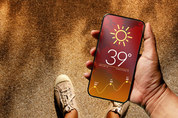 Ecology and Technology Concept. High Temperature Weather show on Mobile Screen on Hot Sunny Day. Top View, Grunge Dirty Concrete Floor with Sunlight as background