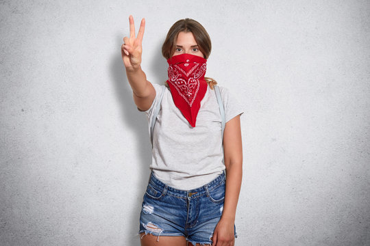 Active confident woman standing isolated over grey background in studio, raising arm, making gesture, showing peace sign, covering her mouth with red bandana, wearing casual items of clothes.