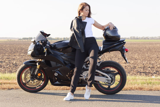 Full length portrait of attractive good looking female looking aside, standing near her vehicle, putting her arm on helmet, wearing leather jacket, white t shirt, black trousers and white sneakers.