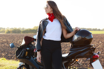 Outdoor shot of confident risky young woman standing near her motorbike, putting hand on helmet, wearing red bandana, white shirt, leather jacket and black trousers. Motorcycle tourism concept.