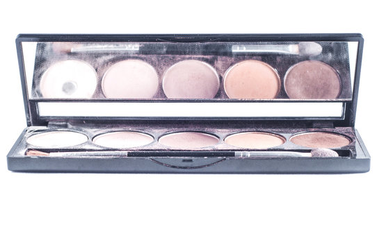 Palette with different shades of face shadows and brush applicator for application. Makeup set with a mirror on a white background, isolate.