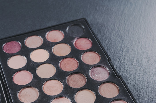 Palette with different shades of face shadows and brush applicator for application. Makeup set on a stone background.