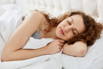 Close up morning portrait of attractive young sensual woman laying on white bed close her eyes, female has long curly hair and pretty face, sleeping with calm facial expression. Recreation concept.
