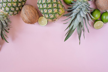 Summer composition. Tropical fruits - pineapple, coconut, lime on pastel pink background. Summer concept. Flat lay, top view, copy space