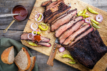 Traditional smoked barbecue wagyu beef brisket offered with farmhouse bread as top view on an old cutting board with Louisiana sauce, onion rings and peperoni Wall mural
