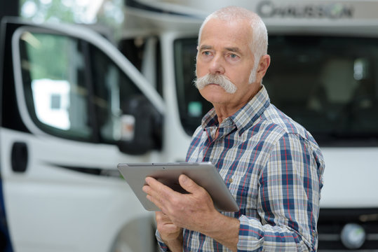 senior logistics man next to container truck with tablet