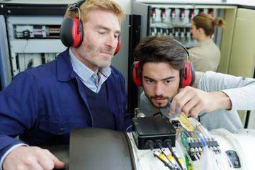male apprentice technician working under supervision