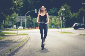Junge Frau mit Elektroroller im Stadtverkehr an Kreuzung mit Ampel  2/2