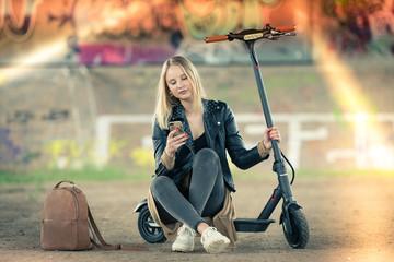Junge Frau sitzt mit Smartphone und elektroroller