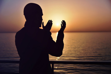 Muslim prayer in the ship praying at sunset with hands up. A silhouette of islamic praying at sunset fom the big ship.