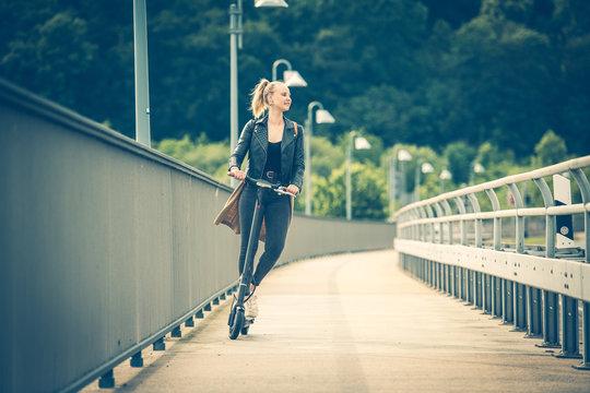 Junge Frau fährt mit Elektroroller auf Radweg über Brücke 1/2