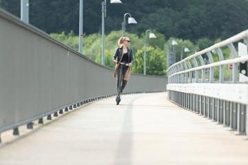 Junge Frau fährt mit Elektroroller auf Radweg über Brücke 2/2