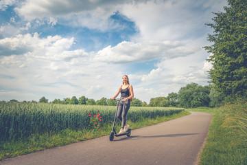 Junge Frau fährt mit Elektroroller auf Radweg am Fuß