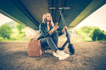 Junge Frau mit Smartphone und Elektroroller