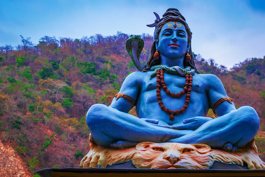 Idol of Indian God Shiva, at the bank of river Ganga in Rishikesh with blurred temple in background , the yoga  capital of India. Indian Tourism