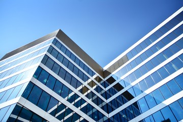 New office building in business center. Wall made of steel and glass with blue sky.  Fotomurales