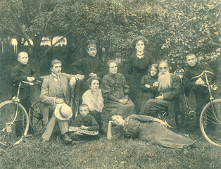 Family photo, family and nine children posing in the background of the garden with two bicycles xylophone