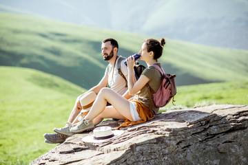 Young couple drinking water while resting on the rock during the travel in the mountains