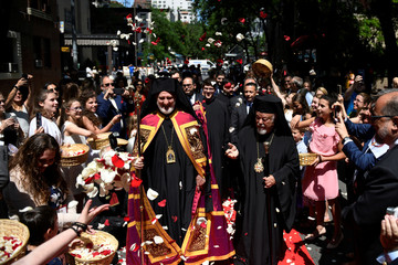 Archbishop Elpidophoros is showered in flowers as he walks down a red carpet to his Enthronement Ceremony in New York