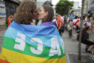 A couple draped with a rainbow flag kisses while attending Bucharest Pride 2019