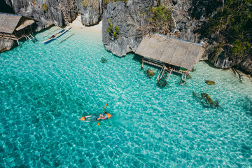Man kayaking in the twin lagoon between the rocks and fishermen houses, enjoying the landscape. Concept about travels in the philippines Wall mural
